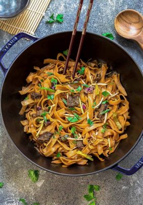 Simple Beef Chow Fun noodles in a blue dish with wooden chopsticks.