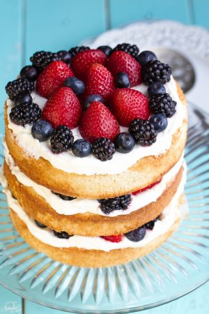 Simple Berries & Cream Sponge Cake topped with blueberries, blackberries and strawberries on a glass cake platter.