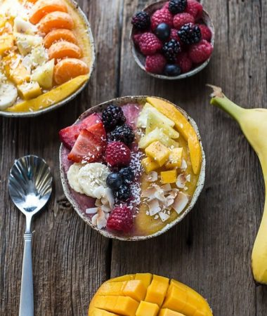 Berry Mango Coconut Layered Smoothie Bowl with fruit and a spoon on a wooden surface