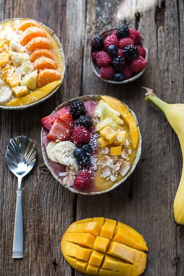 Overhead image of mango smoothie bowl topped with coconut, berries, mango, and bananas.