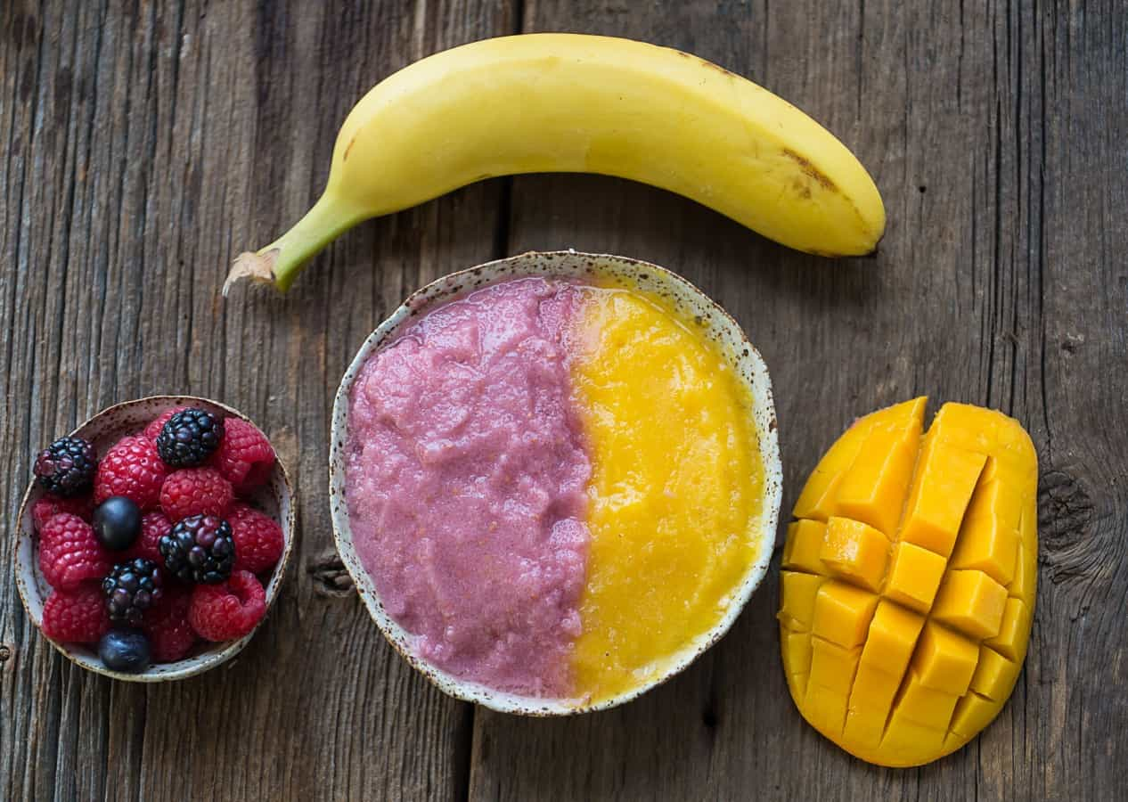 Close-up image of orange and pink berry mango smoothie bowl paired with fresh mango, banana, and berries.
