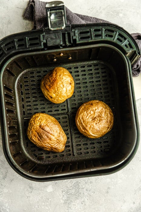 Top view of three baked potatoes in an air fryer basket