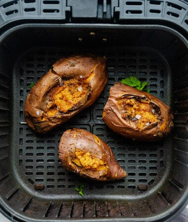 Top view of three baked sweet potatoes in an air fryer basket