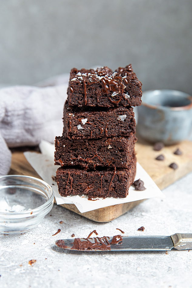 Side view of stacked fudgy paleo flourless brownies on a grey background