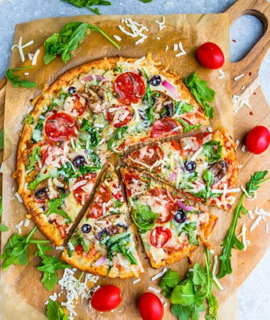 Top view of cauliflower pizza crust on parchment paper with arugula, pepperoni and tomatoes