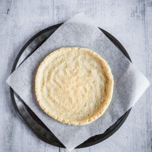 Top view of unbaked cauliflower pizza crust on a parchment paper and pizza stone
