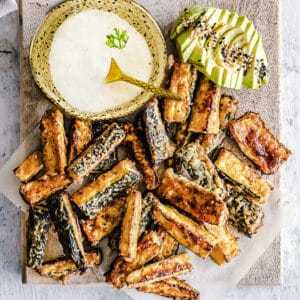 Top view of crispy baked zucchini fries on parchment paper with a bowl of dip and avocado slices