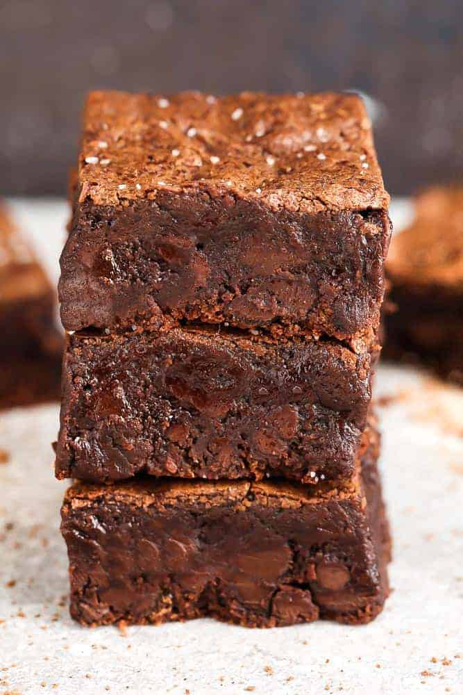 Three delicious and easy brownies stacked on top of each other on a table.