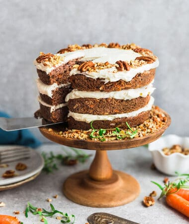 Side view of gluten free Keto Carrot Cake on wooden cake stand with chopped pecans and carrots
