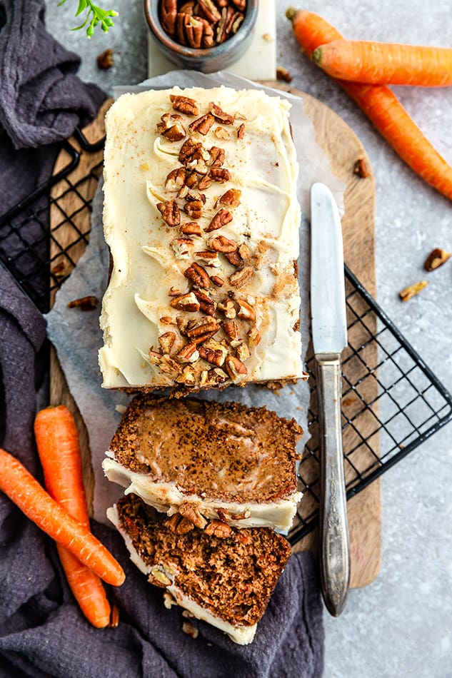 Top view of a paleo carrot cake loaf with two slices on a cutting board on a grey background with a knife and carrots on the side