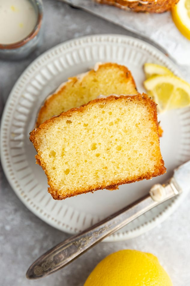 Close-up top view of one slice of gluten free lemon loaf bread on a white plate with a knife