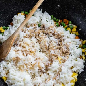 Cooked rice, mixed vegetables, scrambled eggs and the rest of the elements being combined in a large pan