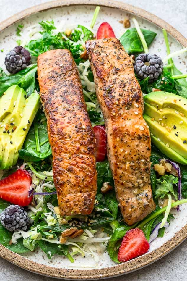 Two pan fried salmon fillets on a bed of mixed greens
