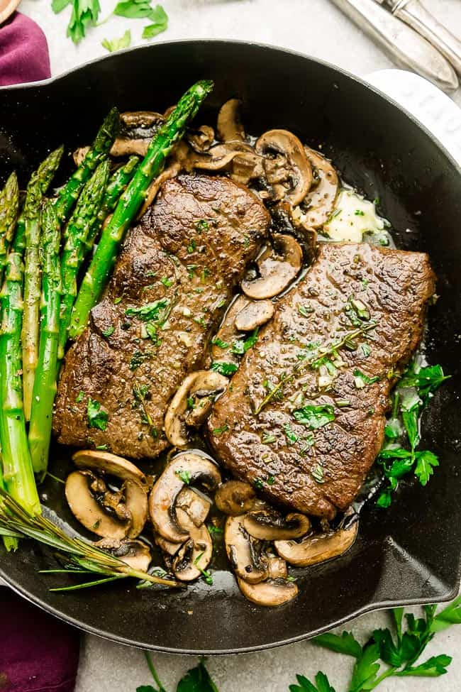 "Garlic Steak with Herb Butter, Asparagus and Mushrooms - pan seared in a skillet plus ""how to"" tips to cook the best tender steak at home. This easy to customize recipe is also gluten free, low carb, paleo and keto friendly."