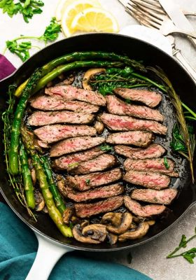 """Garlic Steak with Herb Butter, Asparagus and Mushrooms - pan seared in a skillet plus """"how to"""" tips to cook the best tender steak at home. This easy to customize recipe is also gluten free, low carb, paleo and keto friendly."""