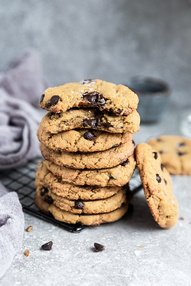 A stack of Vegan Chocolate Chip Cookies with a bite out of the top two
