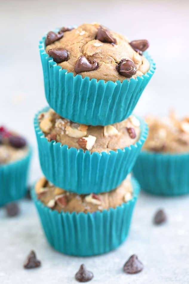 A stack of Easy Blender Muffins with chocolate chips and nuts in teal paper muffin cups