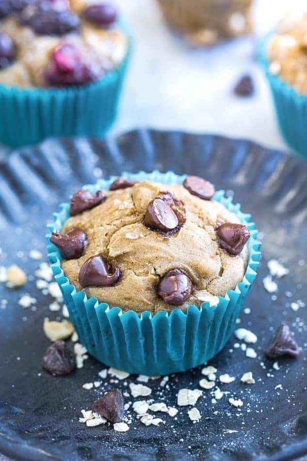 Close-up of a chocolate chip muffin in a blue paper muffin cup on a plate