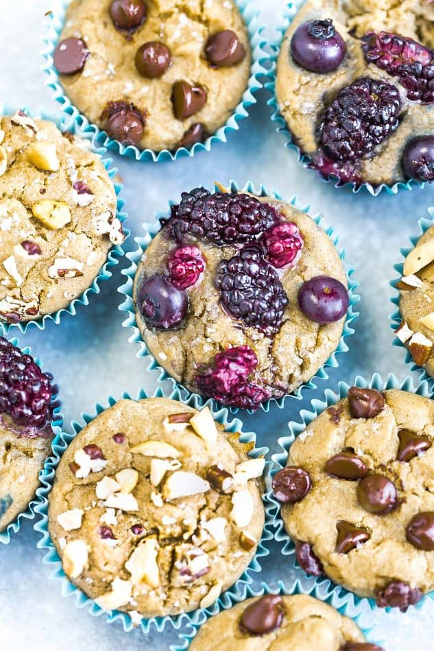 Top view of a variety of muffins with nuts, berries, and chocolate chips