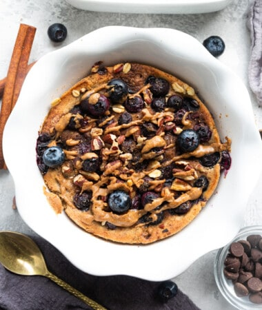 Blueberry Baked Oatmeal on a Table with Chocolate Chips, a Spoon and a Cinnamon Stick