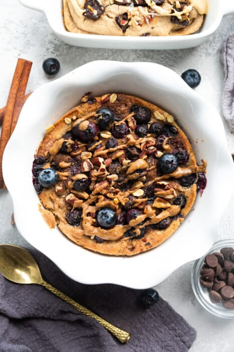 Blueberry Crumble Muffin Baked Oatmeal on a Table with Chocolate Chips, a Spoon and a Cinnamon Stick