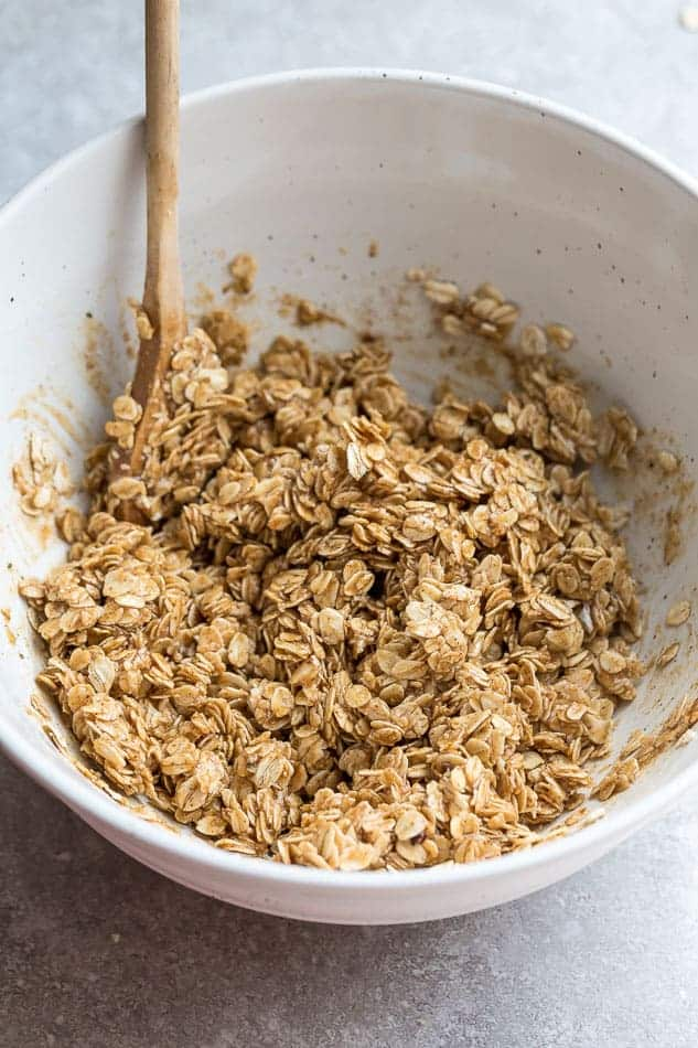 Top view of bowl with oats and a wooden spatula to make breakfast cookies