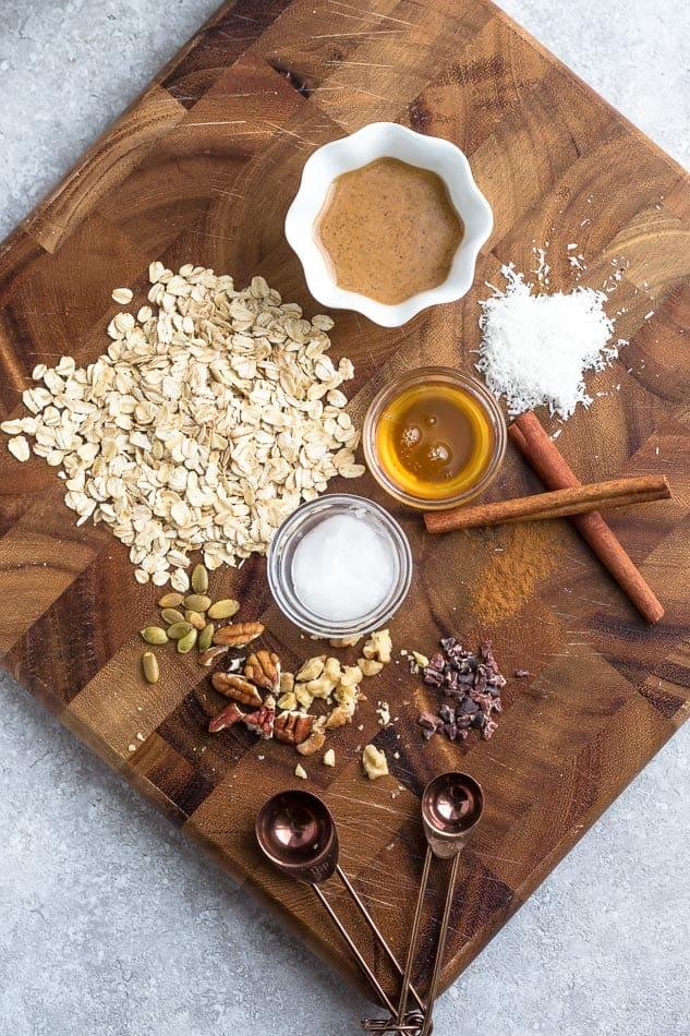 Top view of ingredients to make breakfast cookies - oats, almond butter, cinnamon and sweetener