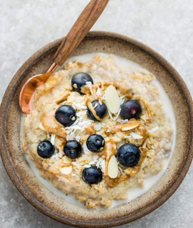 Top view of Blueberry Steel Cut Oats in a ceramic bowl with a spoon