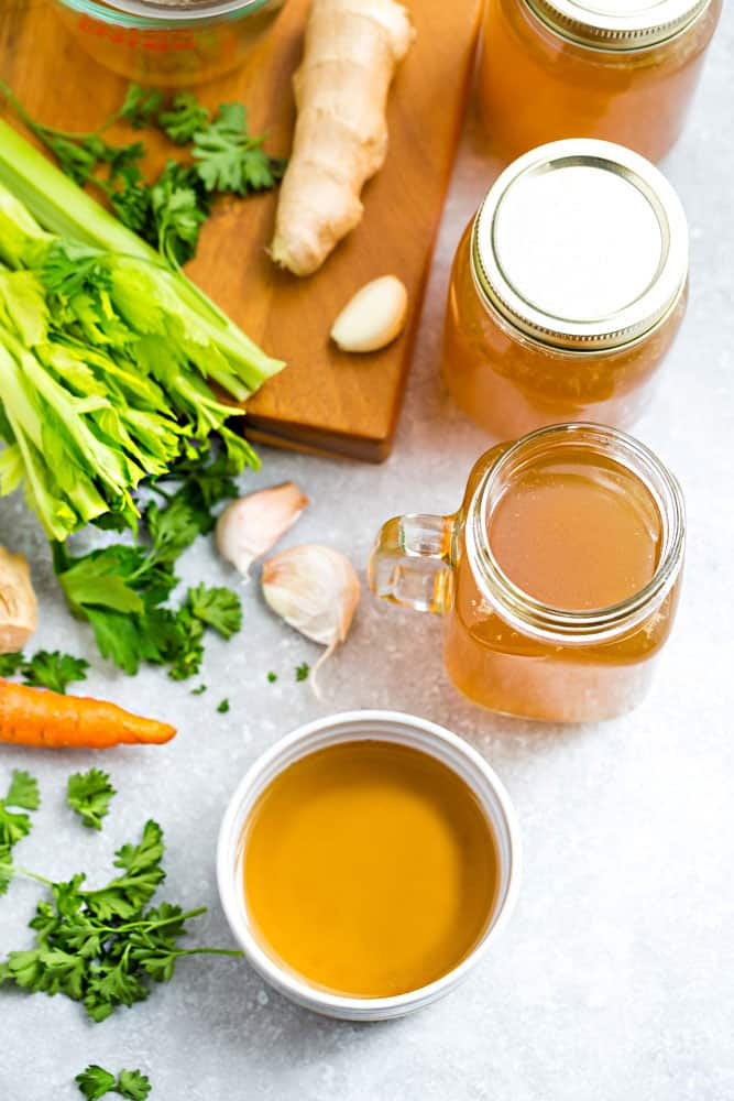 Glass jars of homemade Bone Broth surrounded by ginger, celery, garlic and carrots.
