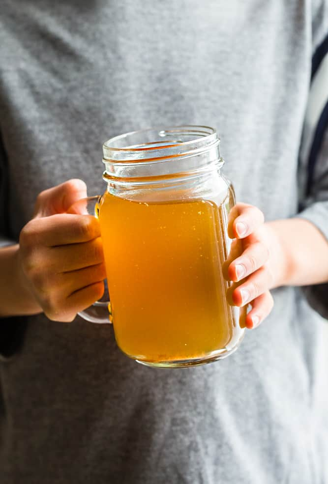 woman holding a glass of delicious Instant Pot Bone Broth.