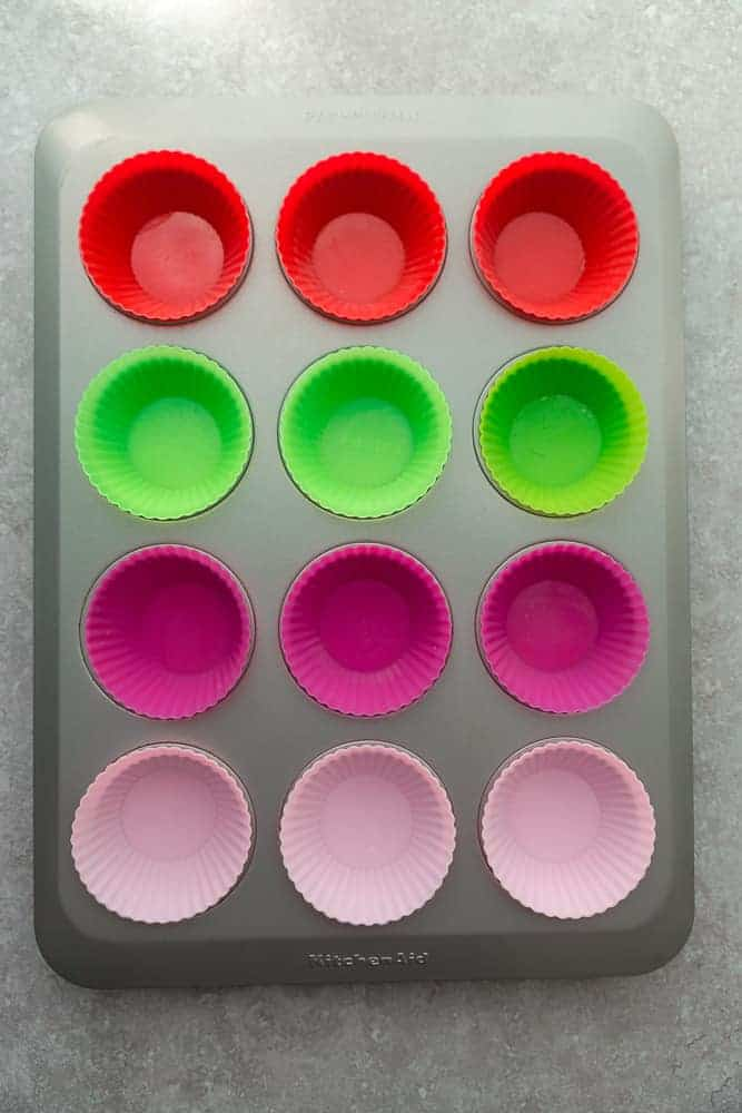 12 Red, Green and Pink Silicone Muffin Liners Inside of a Muffin Tin