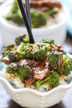 Healthy Beef and Broccoli recipe on a bed of rice in a small white serving bowl with chopsticks.