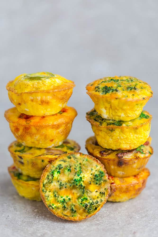 Side view of 9 broccoli egg muffins on a grey background