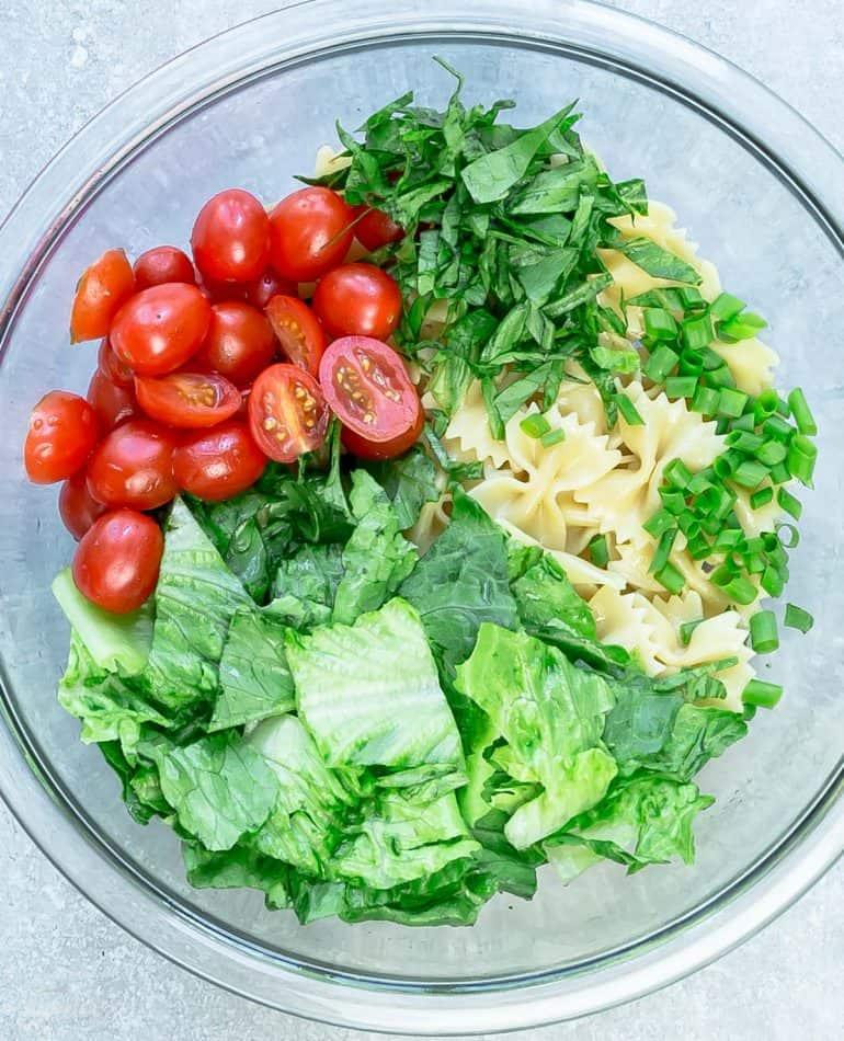 Ingredients for chicken Caesar pasta salad in glass bowl.