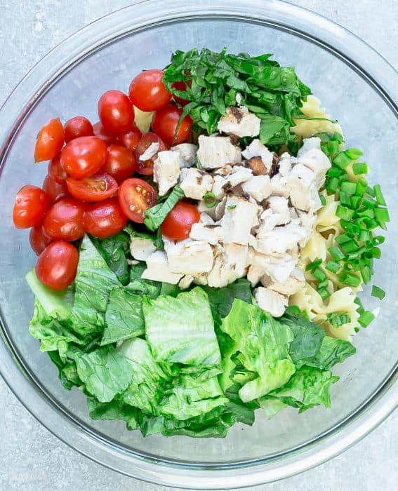 Ingredients for chicken Caesar pasta salad in glass bowl.