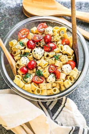 Caprese Pasta Salad - the perfect side dish to bring to summer potlucks, parties, Memorial Day / Fourth of July grillouts/barbecues. Best of all, it's so easy to make and easy to customize with your favorite toppings and homemade dressing. Perfect for Sunday meal prep and leftovers are delicious for school or work lunchboxes or lunchbowls.