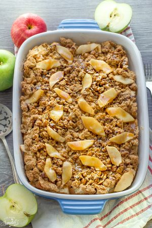Caramel Apple Streusel French Toast Bake in a white and blue casserole dish surrounded by red and green apples.
