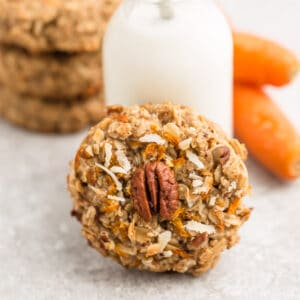 Side view of one healthy carrot cake cookies with a jug of milk behind the cookies