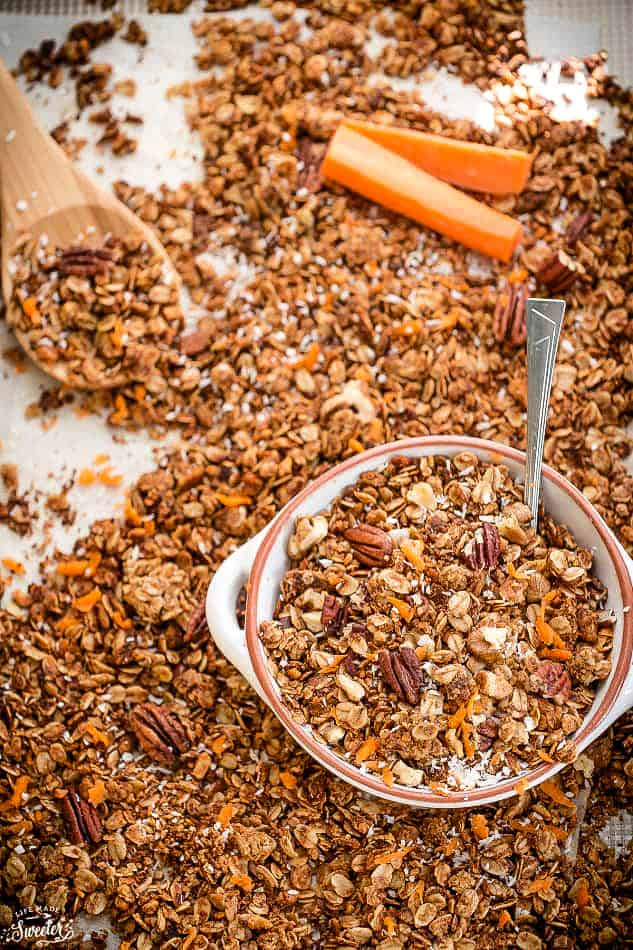 Overhead view of carrot cake granola on a sheet pan with some in a bowl