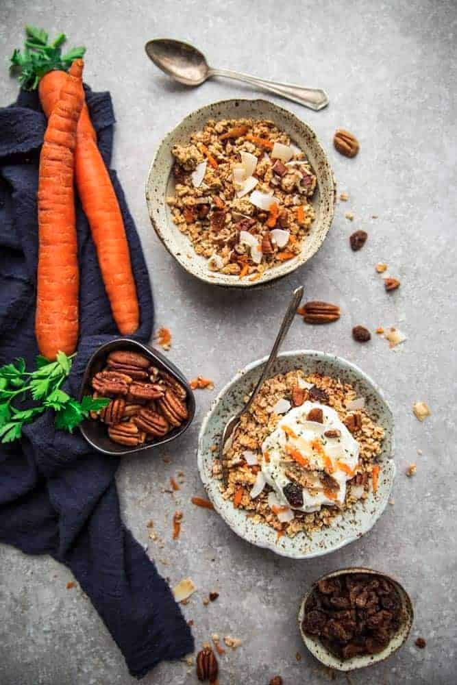 Overhead view of two bowls of Carrot Cake Granola with ingredients nearby