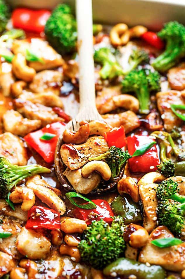 Close-up view of wooden spoon scooping Cashew Chicken and vegetables from a sheet pan