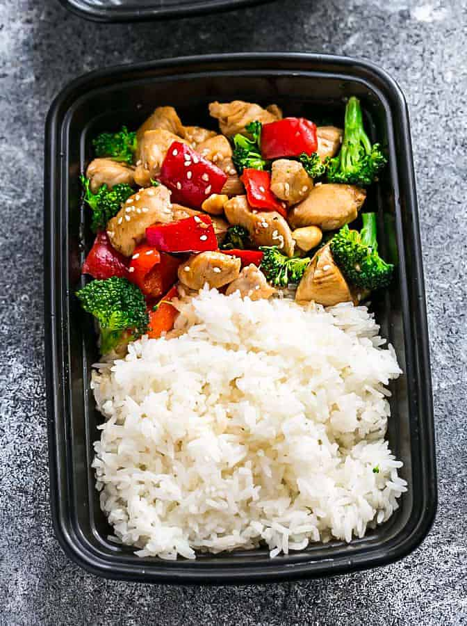 Healthier Cashew Chicken with white rice in a black meal prep container.