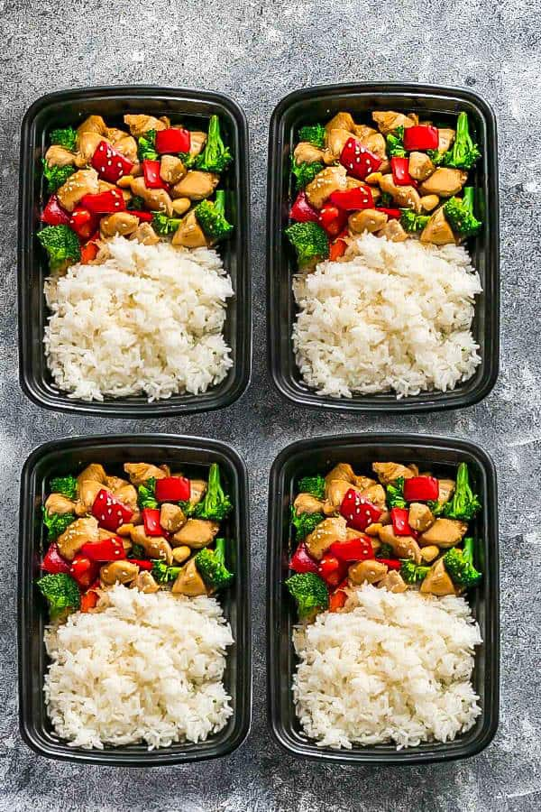 Four meal prepping bowls of Take out Cashew Chicken and white rice.