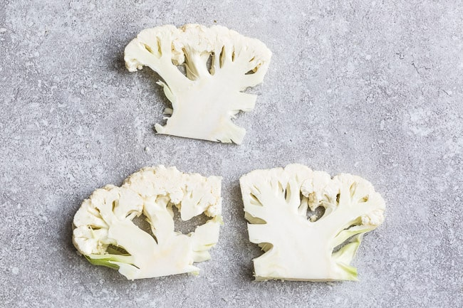 Close-up view of cauliflower florets on a grey background with a knife