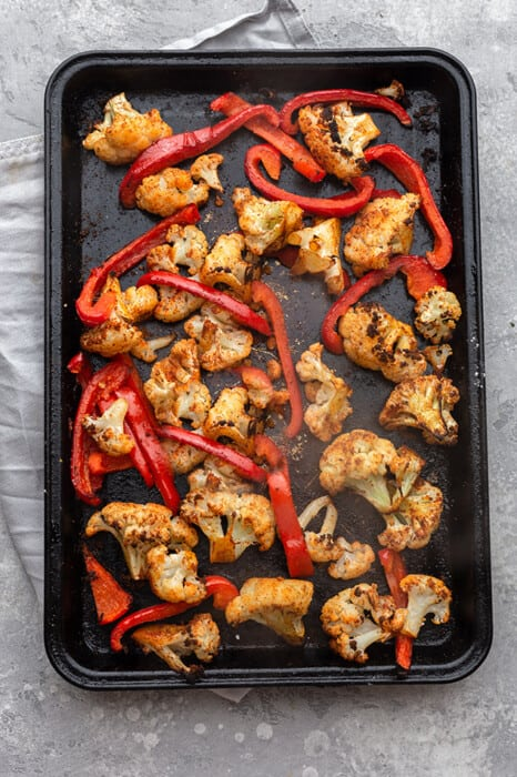 Overhead view of roasted cauliflower and red bell pepper strips on a baking sheet