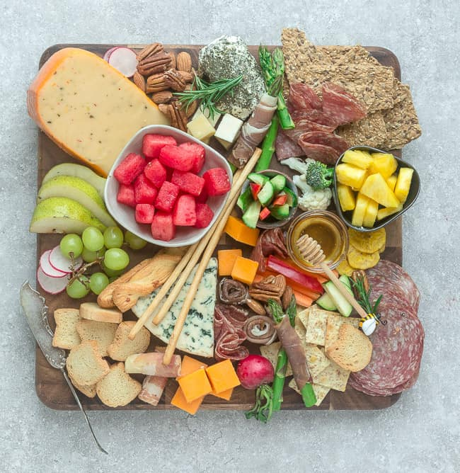Top view of a Charcuterie and Cheese board with crackers, fruits, meats and cheeses
