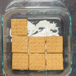 Graham crackers layered over cheesecake filling in a square baking dish