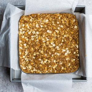Baked, Uncut Granola Bars in a Pan Lined with Overhanging Parchment Paper