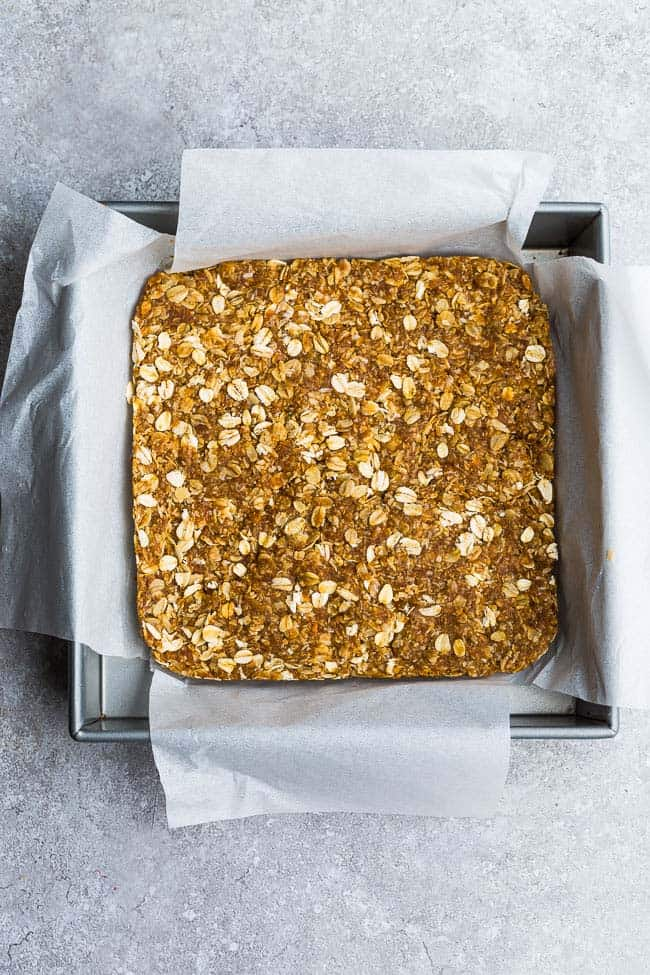 Top view of a parchment-lined square pan of homemade granola bars
