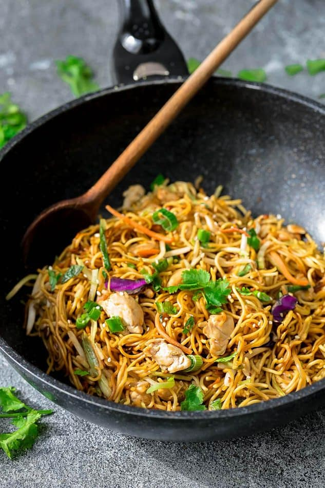 Side view of Chicken Chow Mein in a wok with a wooden spoon